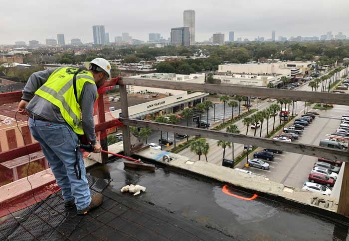 A technician administers an eld test on a roof system—z6 consulting